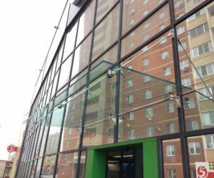 Установка цельностеклянного козырька на фасад